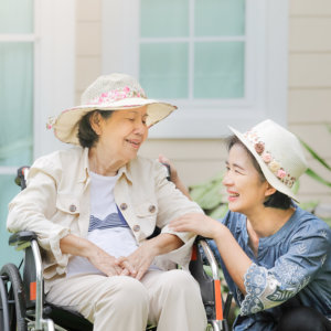 caregiver and old woman cheerfully talking