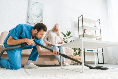 caregiver using vacuum cleaner while senior woman sitting on sofa