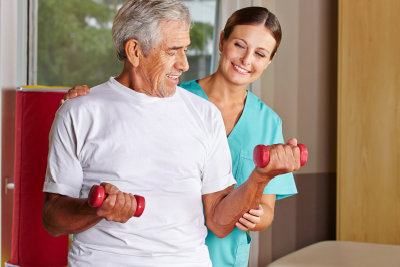 therapist assisting senior man with dumbbells