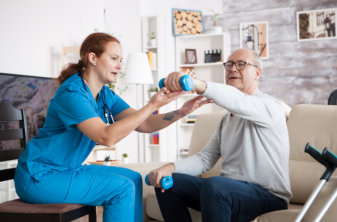 physiotherapist assisting senior man in exercising