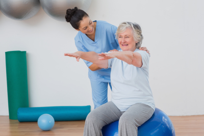 physical therapist assisting a senior woman sitting on an exercise ball