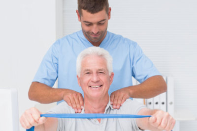 male physiotherapist assisting senior man in exercising with resistance band
