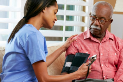 female nurse doing blood pressure monitoring for senior man